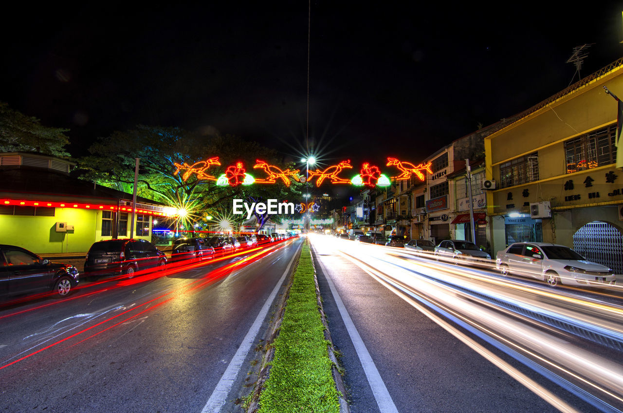 illuminated, motion, transportation, night, architecture, speed, city, long exposure, road, street, light trail, mode of transportation, blurred motion, building exterior, built structure, city life, no people, land vehicle, city street, direction, outdoors, diminishing perspective