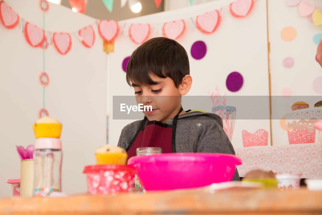 childhood, child, one person, boys, indoors, real people, lifestyles, men, table, males, looking, front view, casual clothing, headshot, leisure activity, selective focus, sitting, innocence
