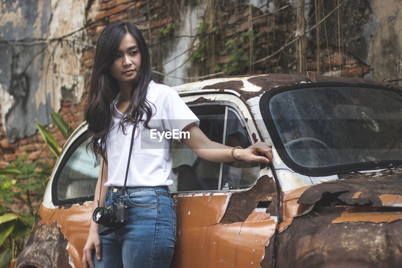 Young Woman Standing By Abandoned Car