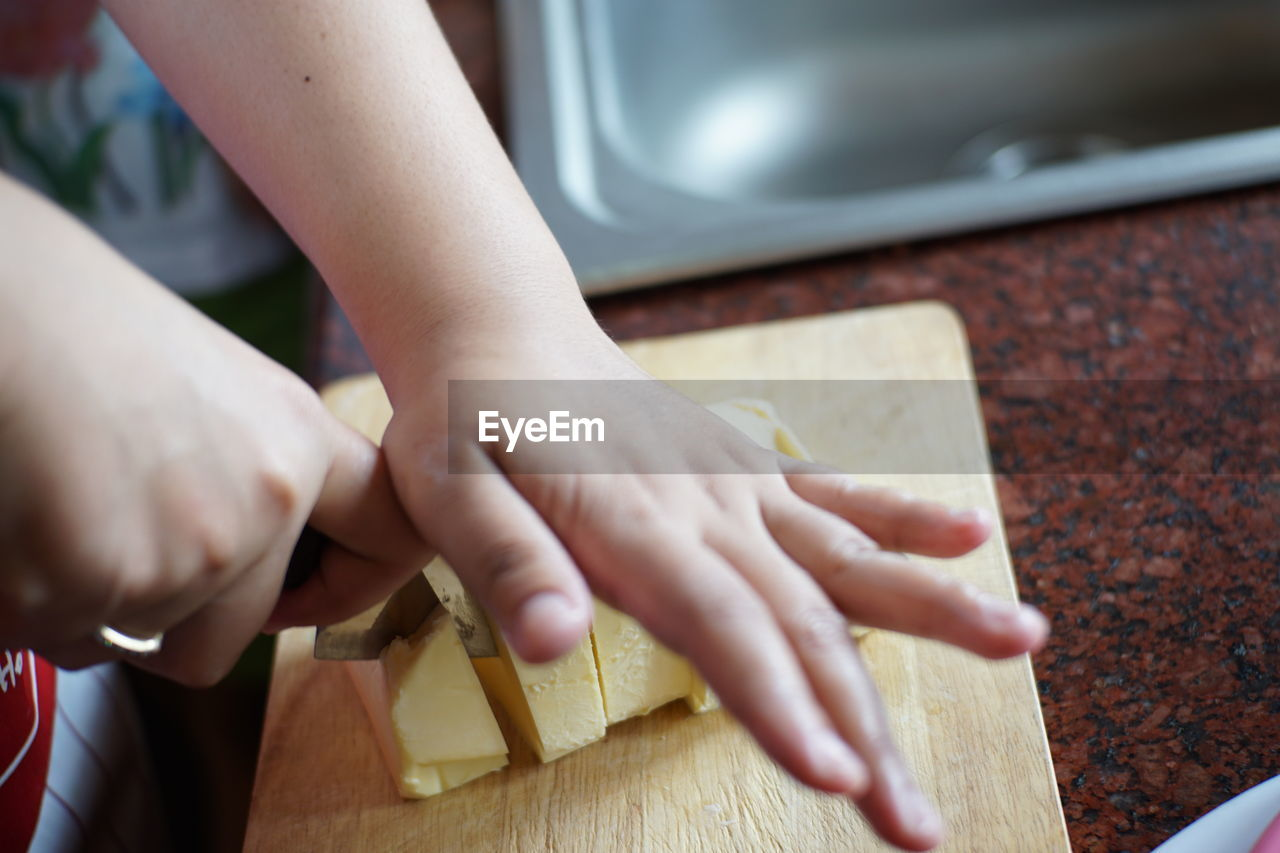 Cropped hands of person cutting food on board in kitchen