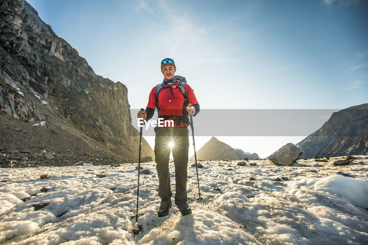 MAN STANDING ON SNOW COVERED MOUNTAIN