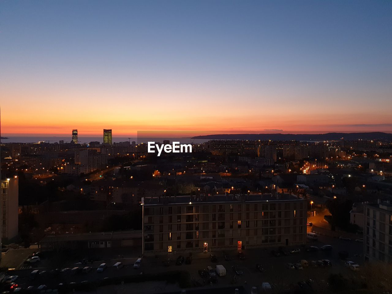 building exterior, sky, city, built structure, architecture, cityscape, sunset, orange color, building, no people, nature, illuminated, copy space, high angle view, residential district, outdoors, clear sky, city life, office building exterior, skyscraper