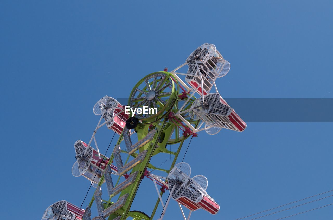 low angle view, sky, nature, clear sky, arts culture and entertainment, blue, day, amusement park ride, metal, amusement park, no people, spinning, outdoors, sunlight, ferris wheel, copy space, built structure, tall - high, shape, positive emotion