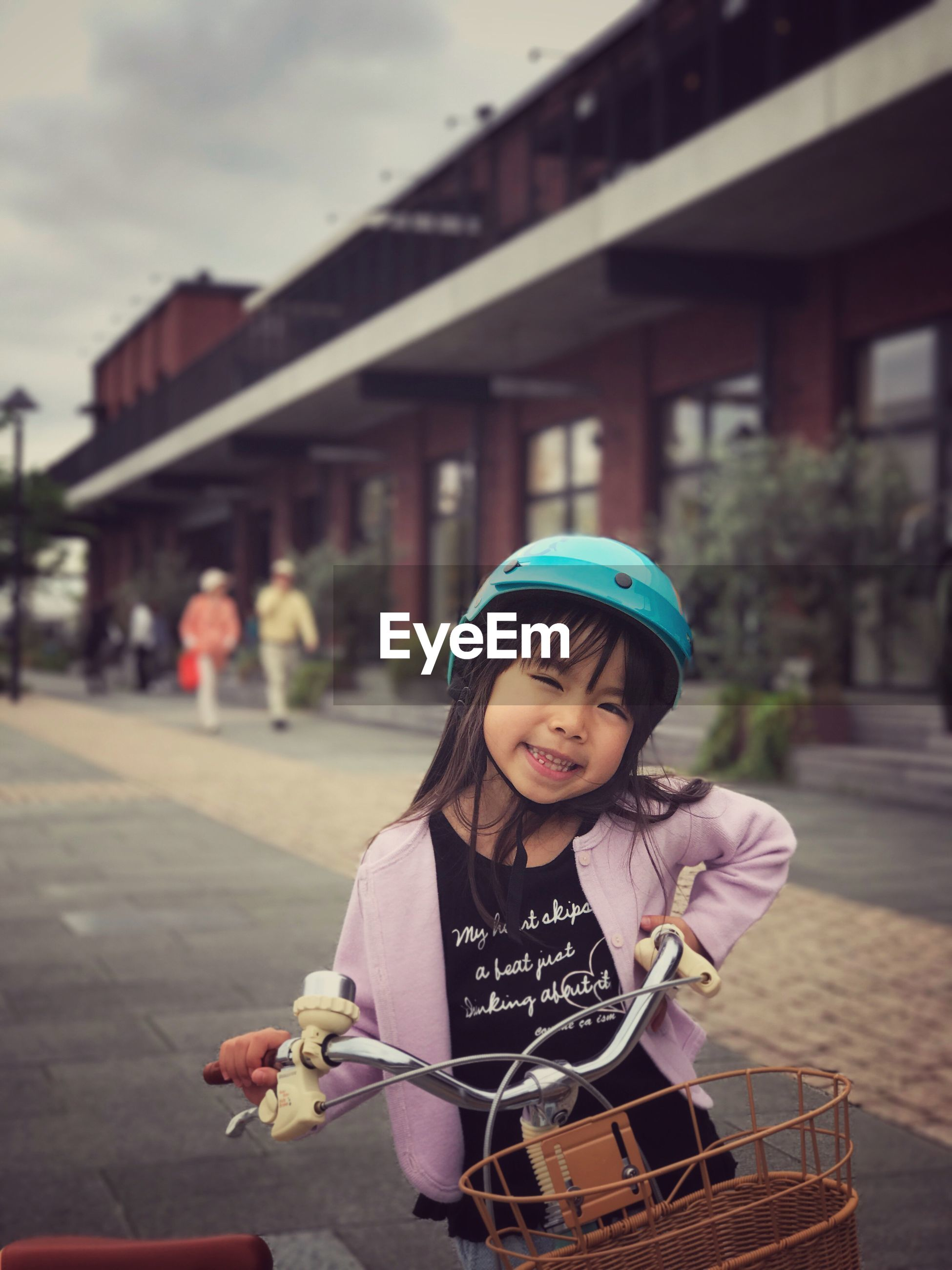Portrait of girl with bicycle on street in city