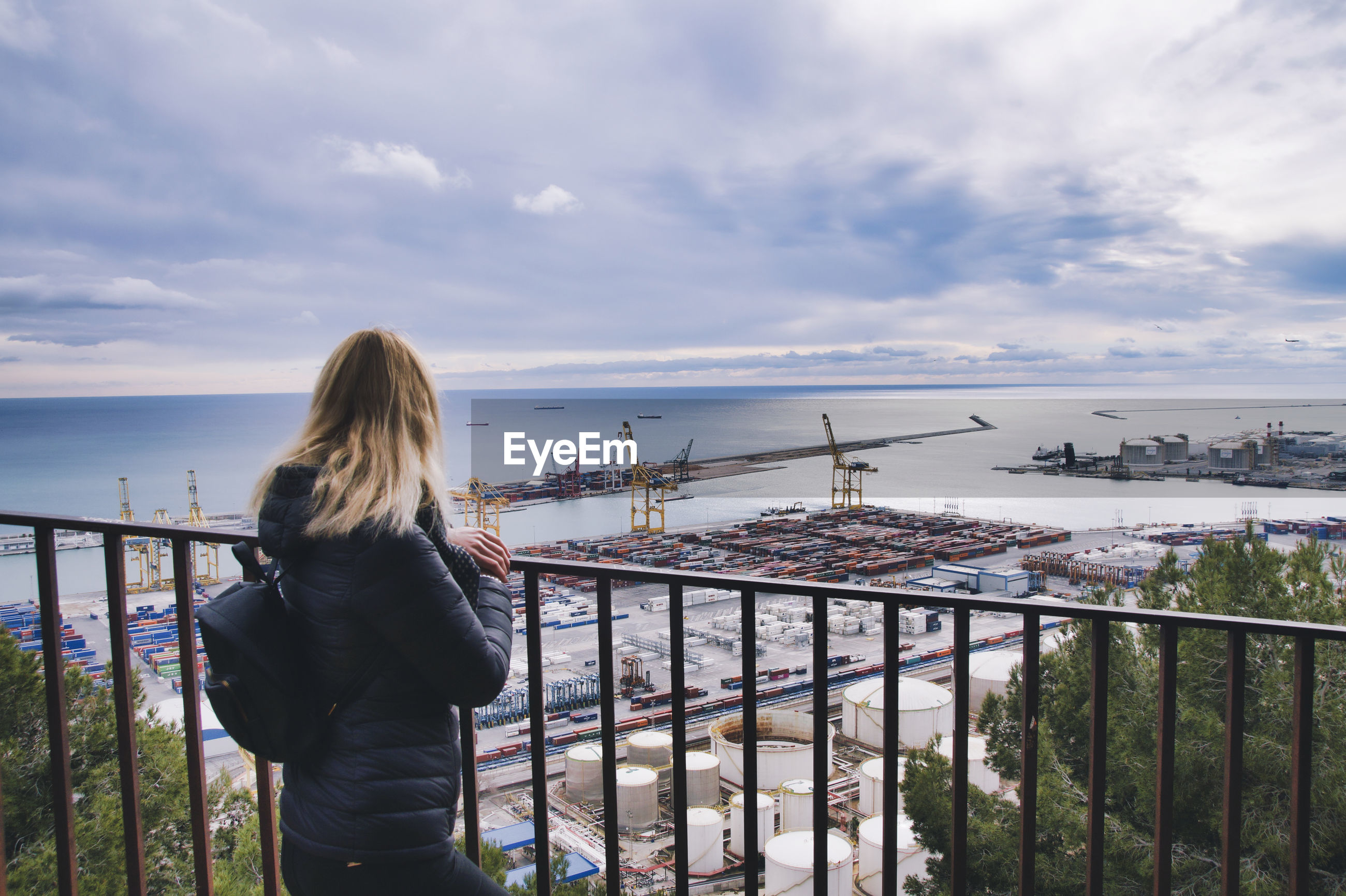 Woman looking at sea against cloudy sky