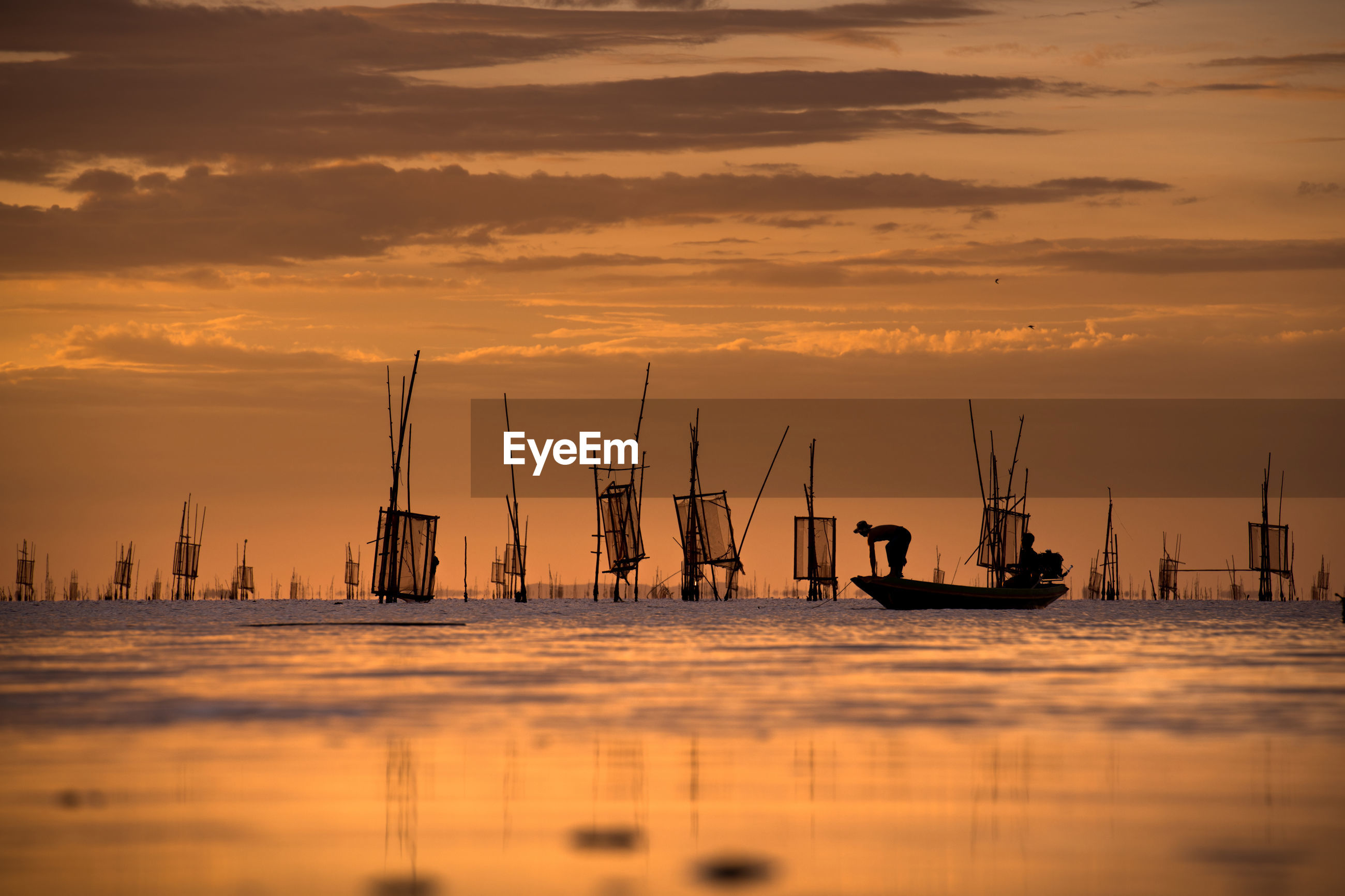 Silhouette men on sailboat in sea against sky during sunset