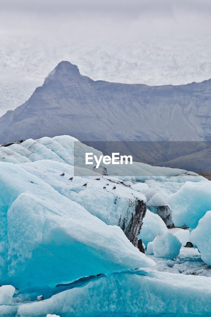 Scenic View Of Snowcapped Mountains And Icebergs