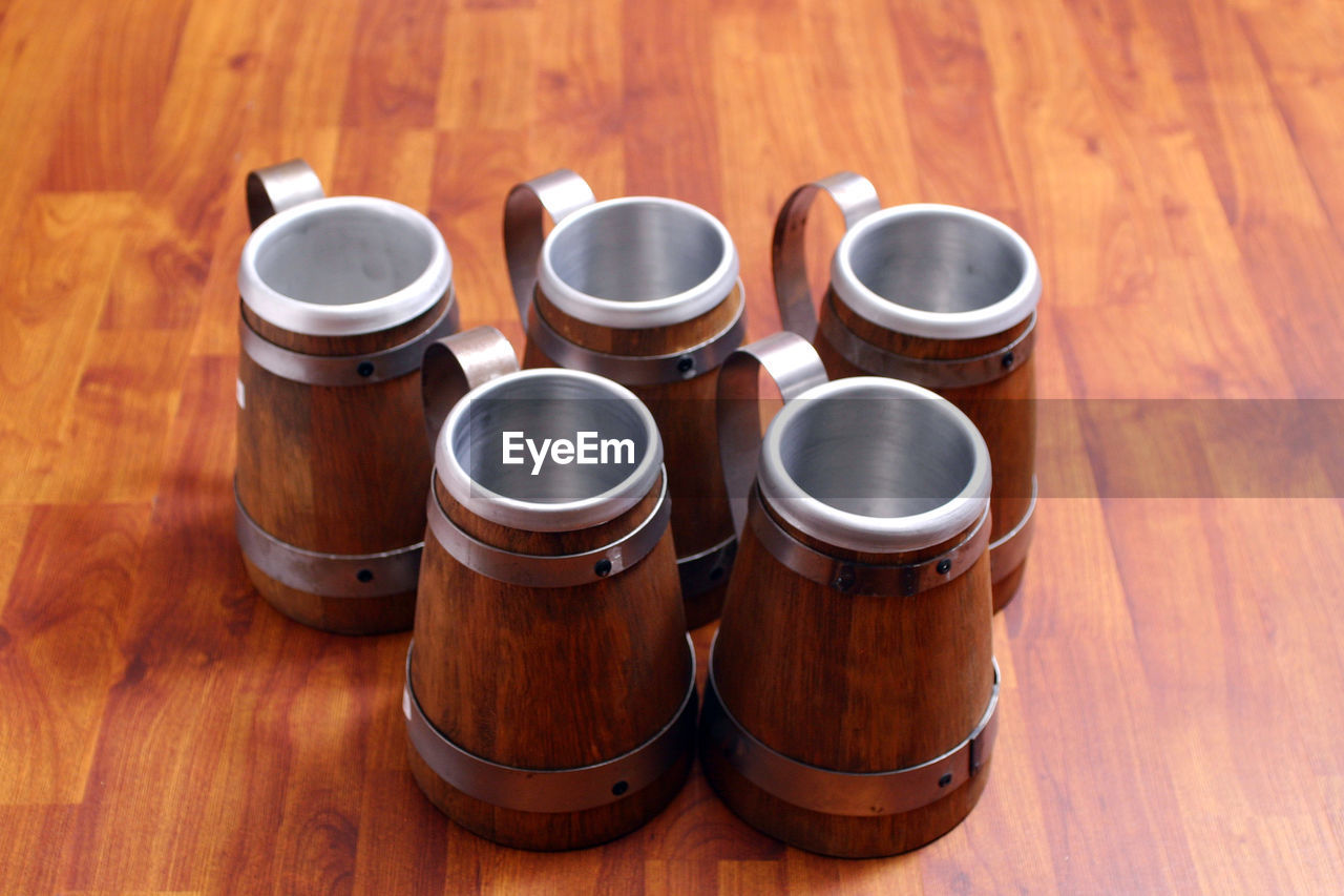 wood - material, table, brown, indoors, wood, no people, still life, high angle view, drink, group of objects, refreshment, food and drink, cylinder, close-up, focus on foreground, metal, beer - alcohol, side by side, shiny, barrel, silver colored, wood grain