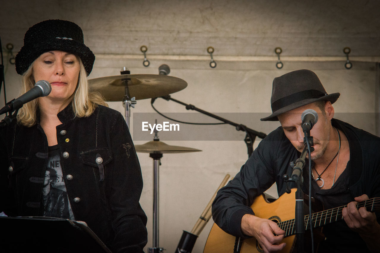 music, performance, singing, hat, musician, playing, singer, arts culture and entertainment, microphone, musical instrument, guitar, performance group, indoors, technology, young adult, people, adult