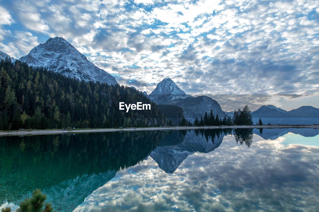 Idyllic shot of mountains against sky reflecting in lake