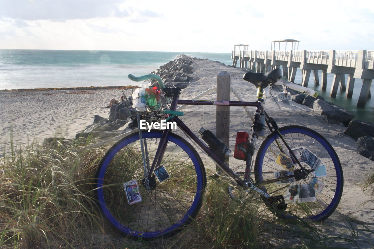 bicycle, sea, day, sky, outdoors, water, horizon over water, nature, transportation, mode of transport, tranquil scene, beach, land vehicle, tranquility, scenics, beauty in nature, no people, grass
