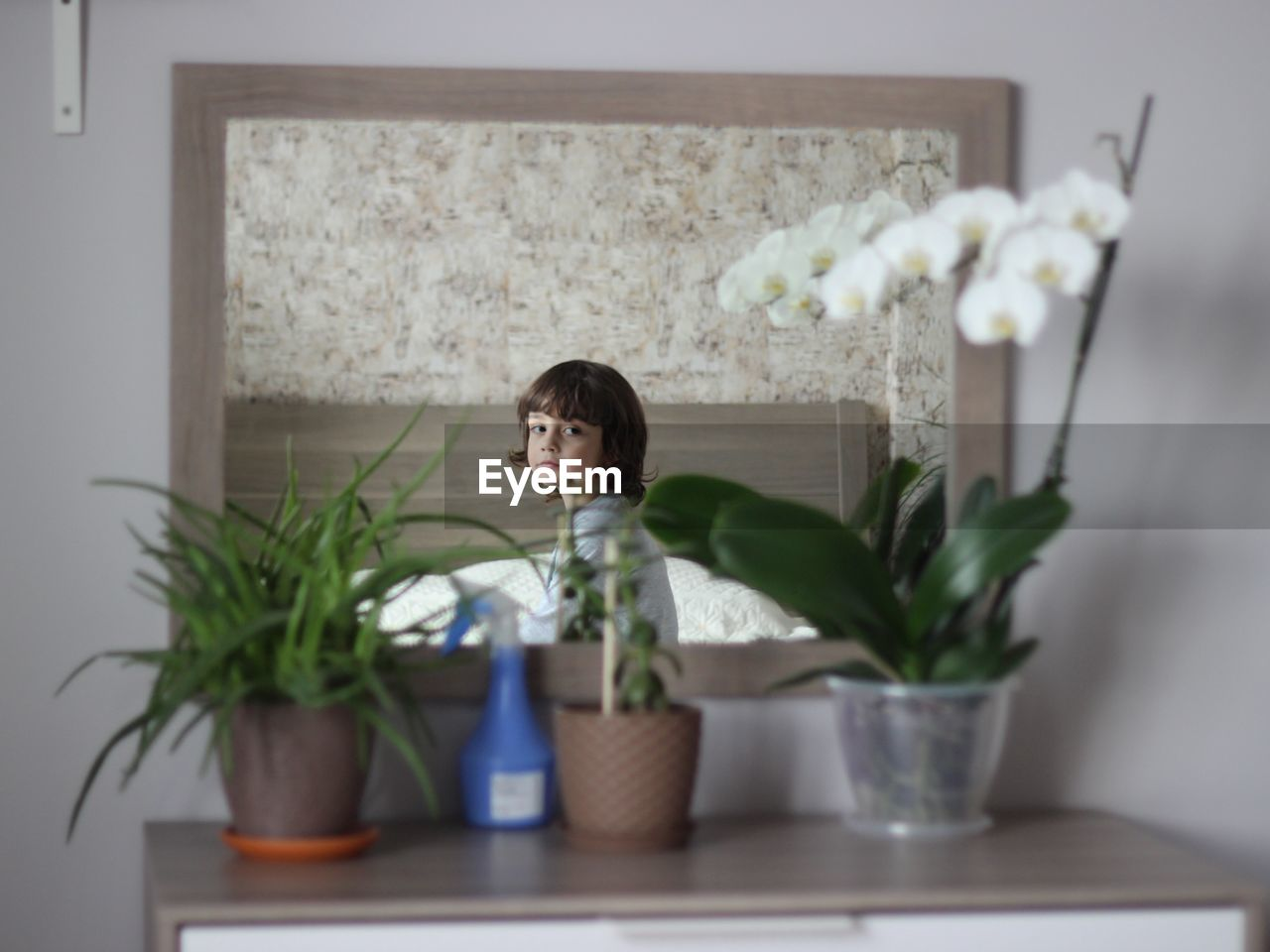 Mirror With Reflection Of Boy Sitting On Bed At Home