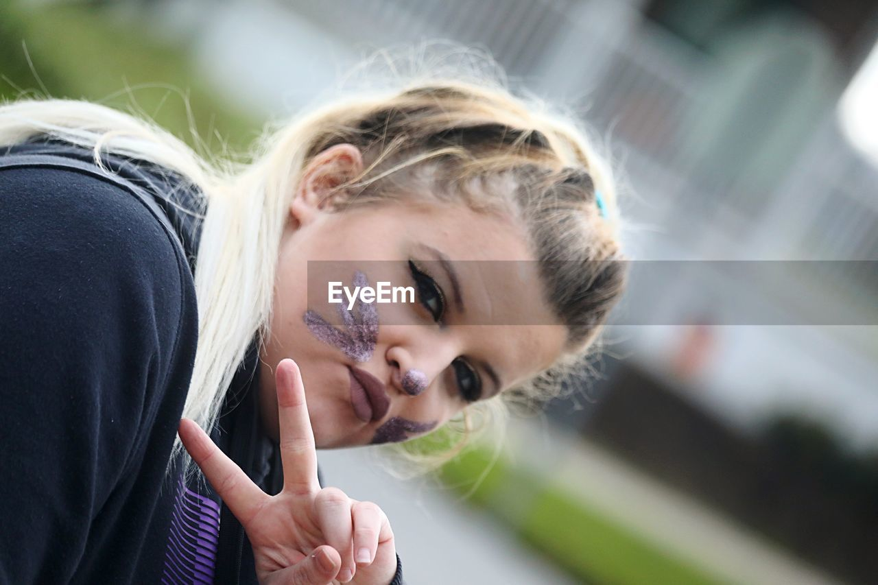 Portrait of young woman with painted face gesturing peace sign