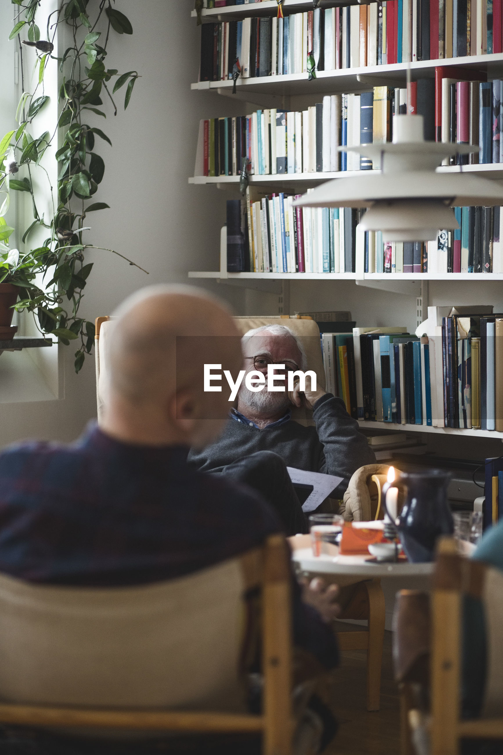 Senior therapist with mature male patient at home office