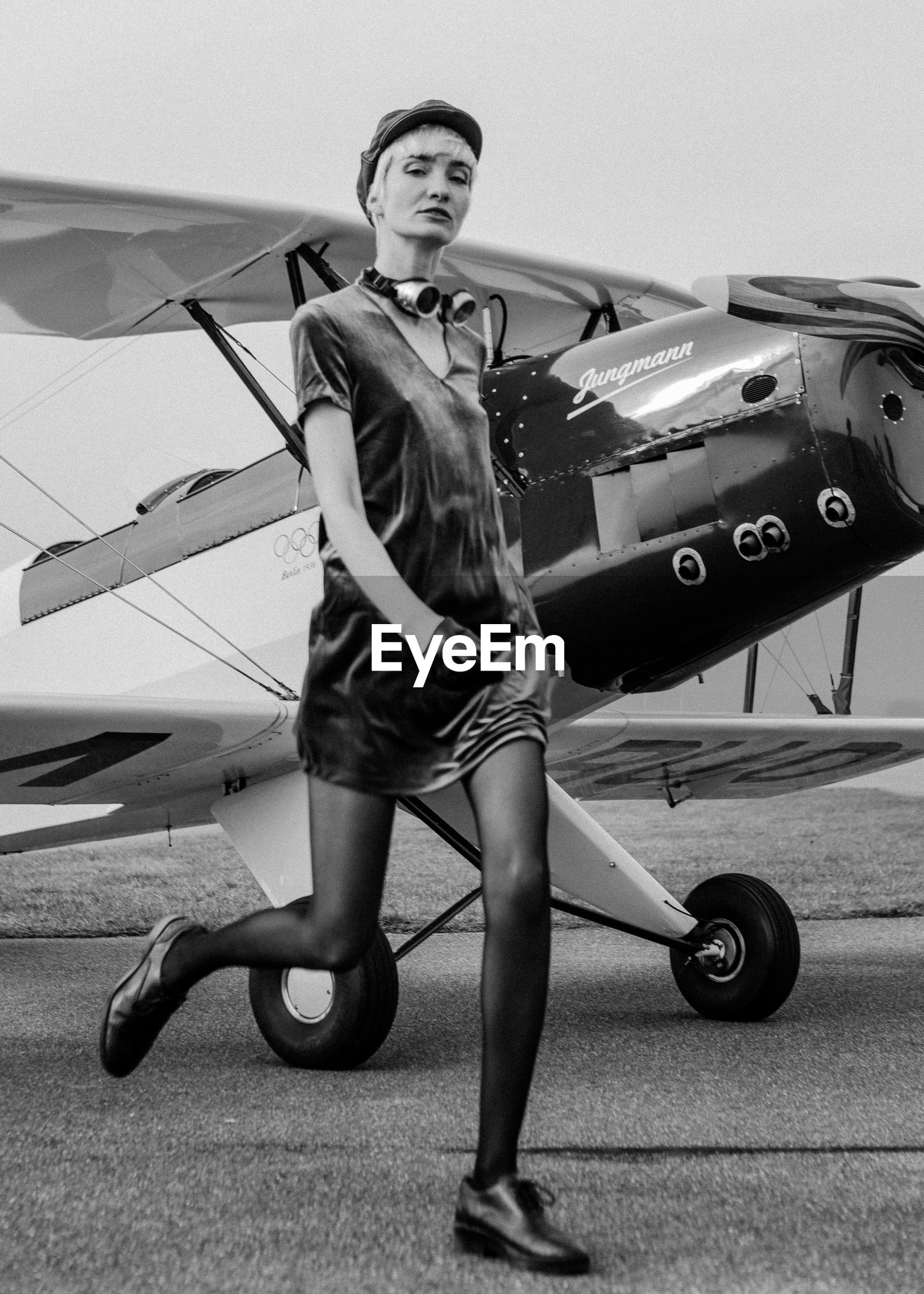 PORTRAIT OF YOUNG WOMAN STANDING BY AIRPLANE AT AIRPORT
