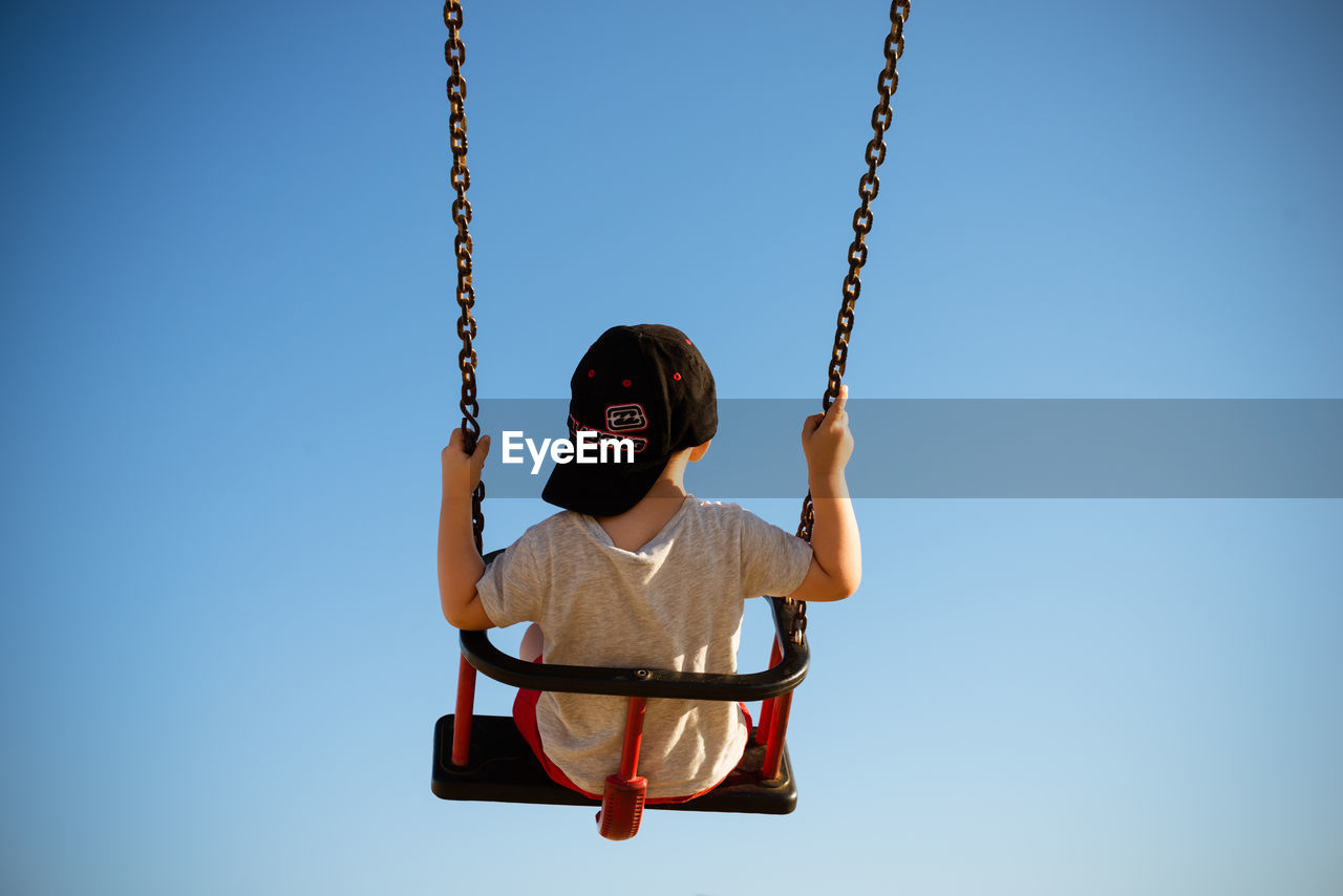 LOW ANGLE VIEW OF BOY ON SWING AT PLAYGROUND