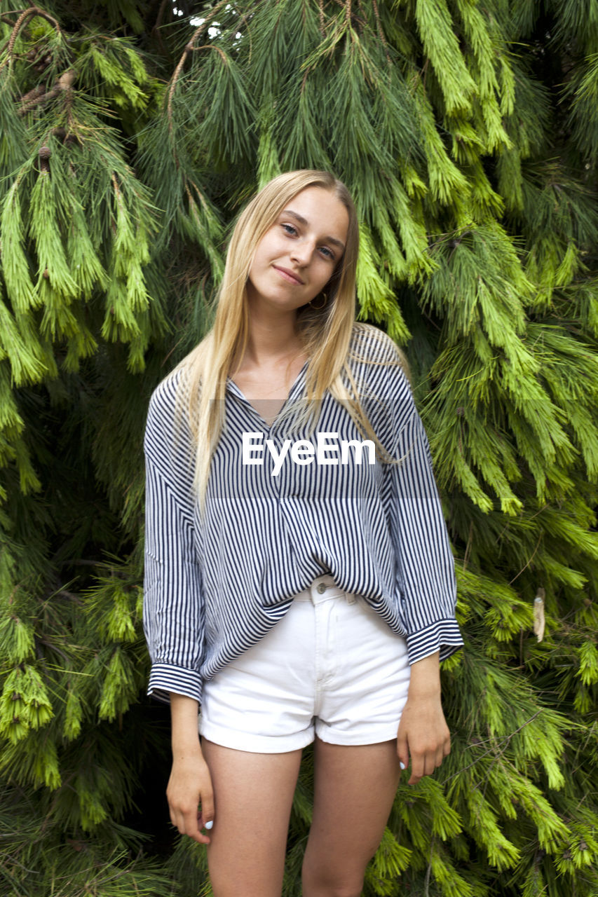 one person, hair, young adult, long hair, young women, hairstyle, plant, front view, blond hair, smiling, real people, lifestyles, casual clothing, three quarter length, happiness, day, beauty, leisure activity, beautiful woman, outdoors, teenager