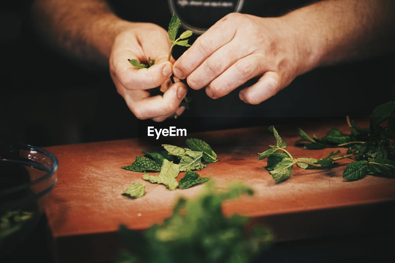 Cropped Image Of Man Plucking Mint Leaves Over Cutting Board At Counter