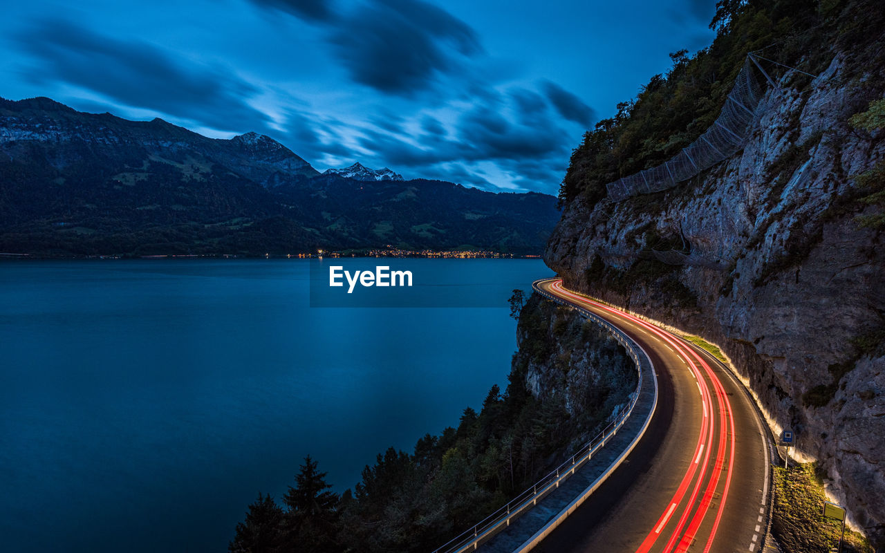Light trails on road by mountain against sky at dusk