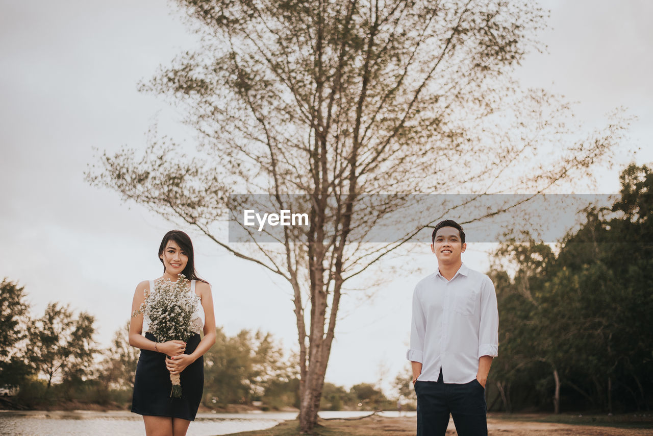 Portrait Of Smiling Young Couple Standing Against Tree