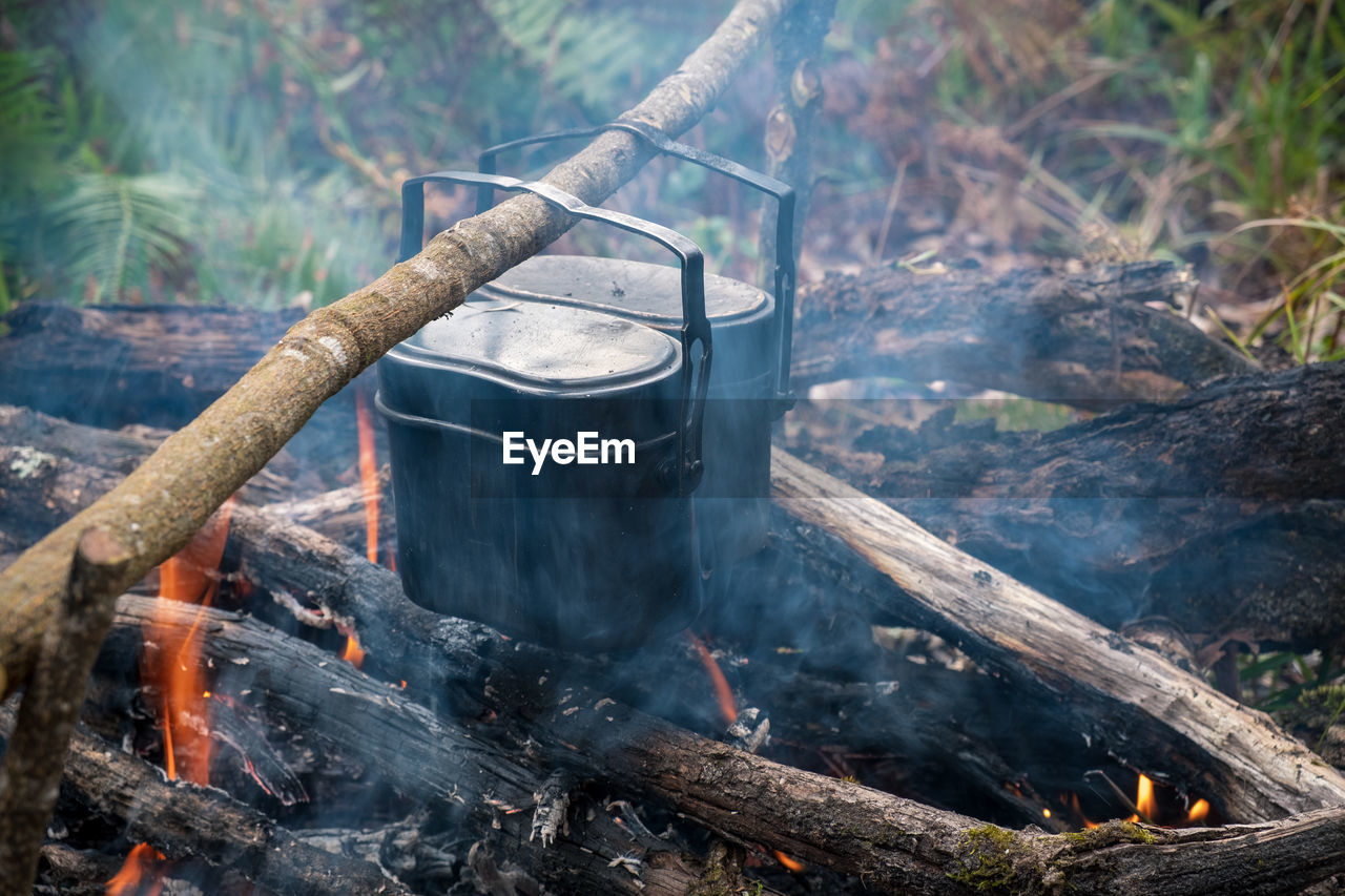 High Angle View Of Food In Containers Cooking Over Campfire