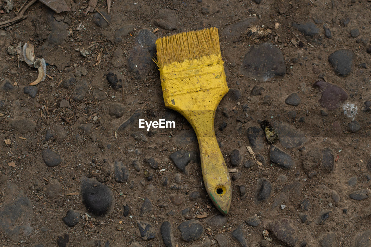 yellow, dirt, high angle view, no people, close-up, land, dirty, nature, day, mud, fruit, outdoors, equipment, brown, work tool, still life, directly above, wet, hand tool, slippery, pollution