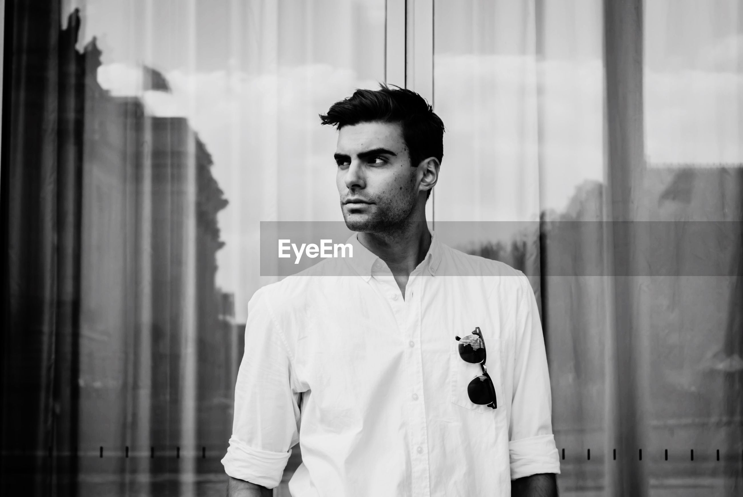 Handsome young man looking away while standing against building