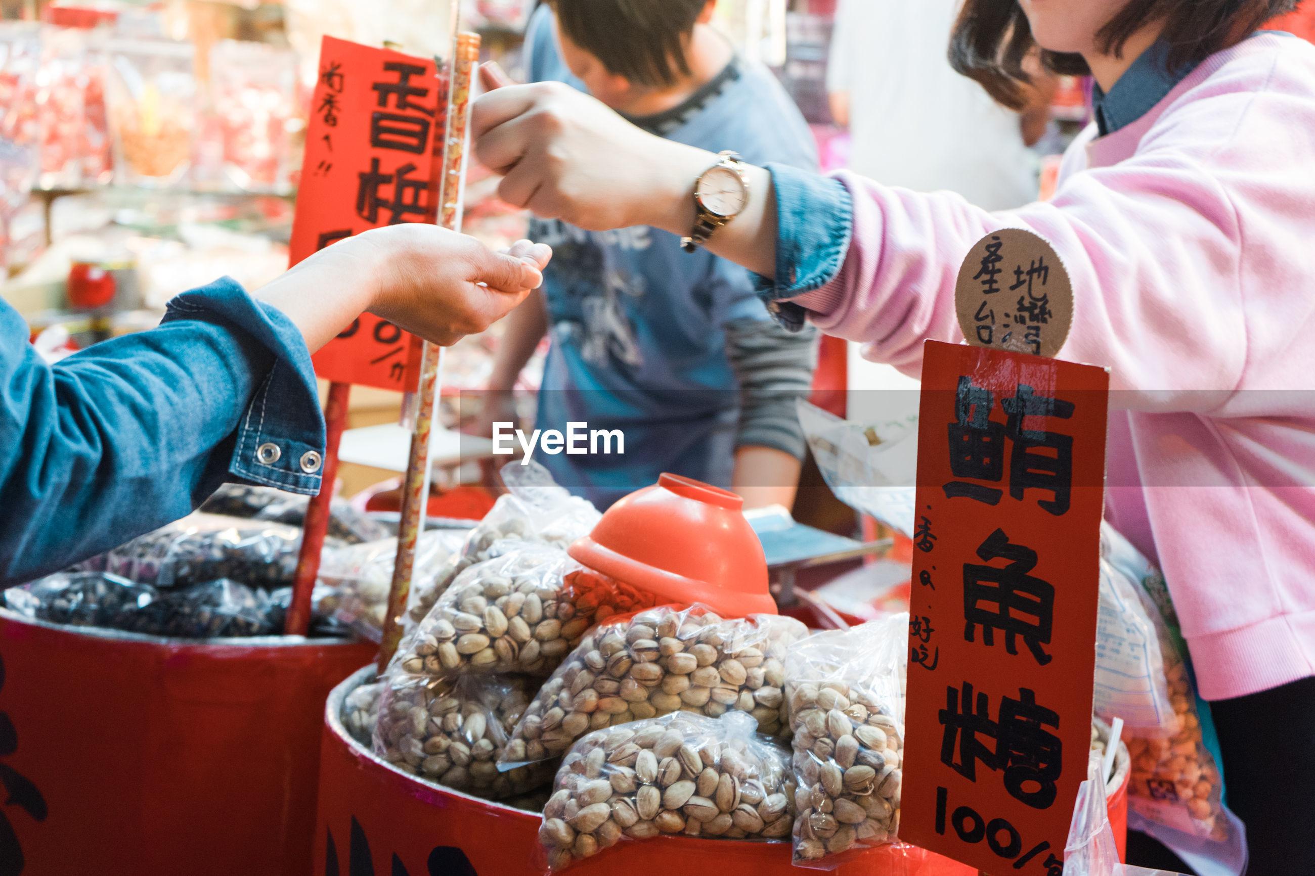 Woman buying pistachio from market vendor