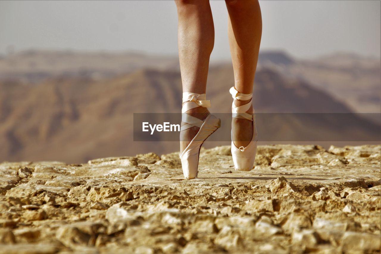 Low section of ballet danger standing tiptoe on rock against mountain