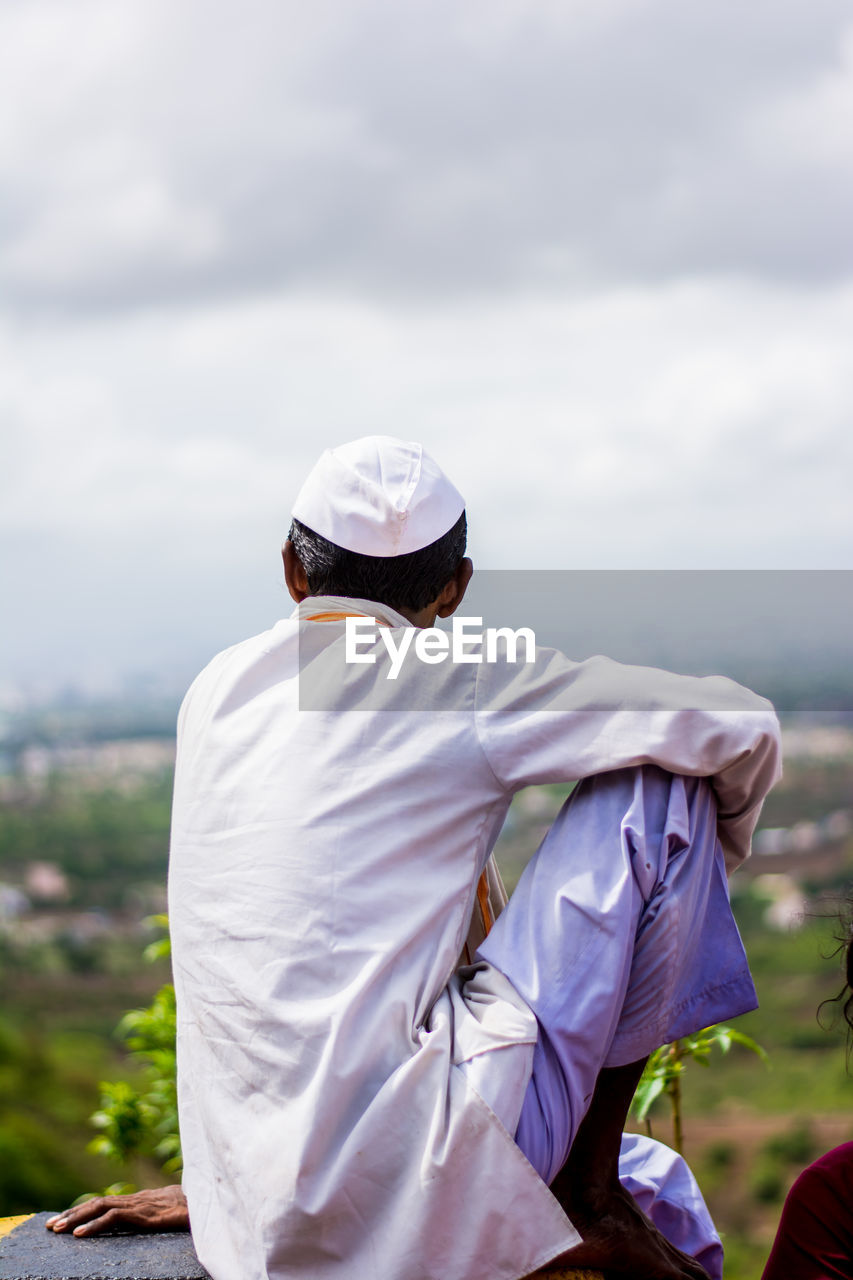 Rear View Of Man Wearing Topi Looking At Field