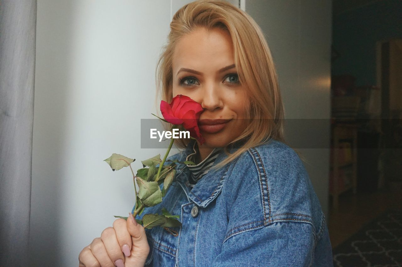 Portrait of woman holding red rose at home