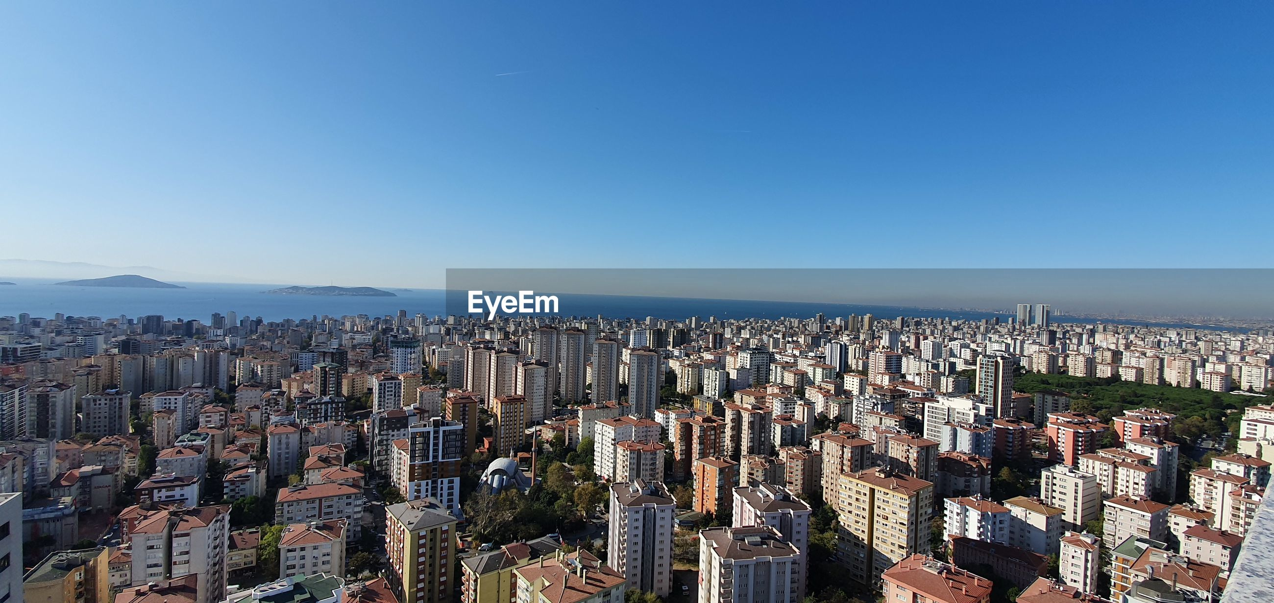 High angle view of city buildings against clear blue sky