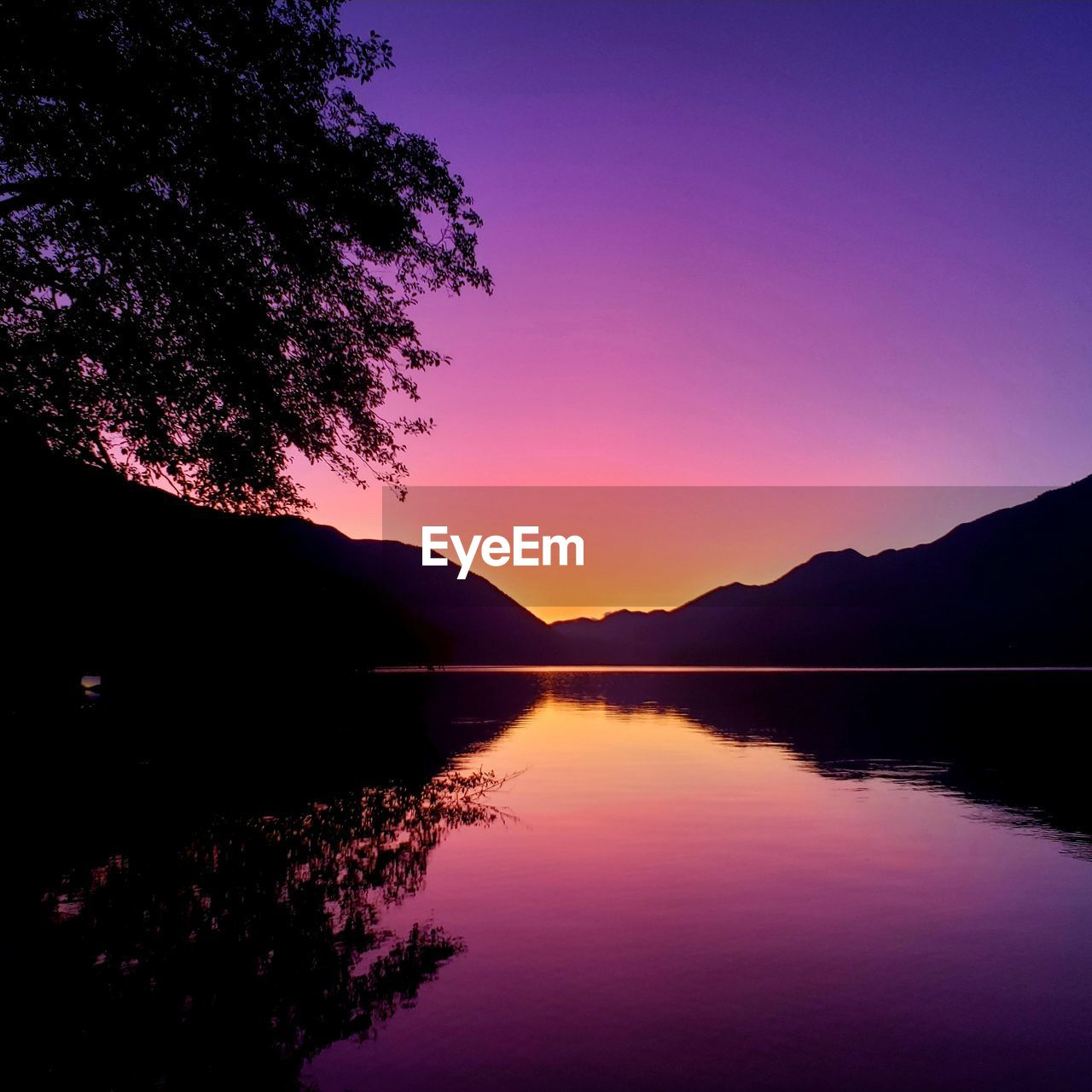 sunset, sky, beauty in nature, water, tranquility, scenics - nature, tranquil scene, reflection, lake, silhouette, tree, mountain, nature, plant, no people, waterfront, idyllic, orange color, purple, outdoors, romantic sky