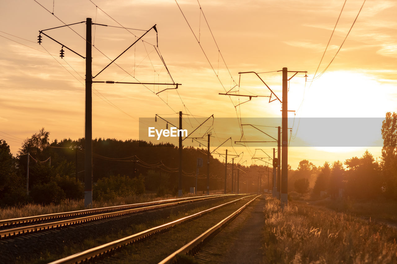 sky, sunset, cable, electricity, rail transportation, railroad track, transportation, track, technology, nature, electricity pylon, fuel and power generation, power supply, power line, tree, orange color, cloud - sky, connection, the way forward, plant, no people, diminishing perspective, outdoors