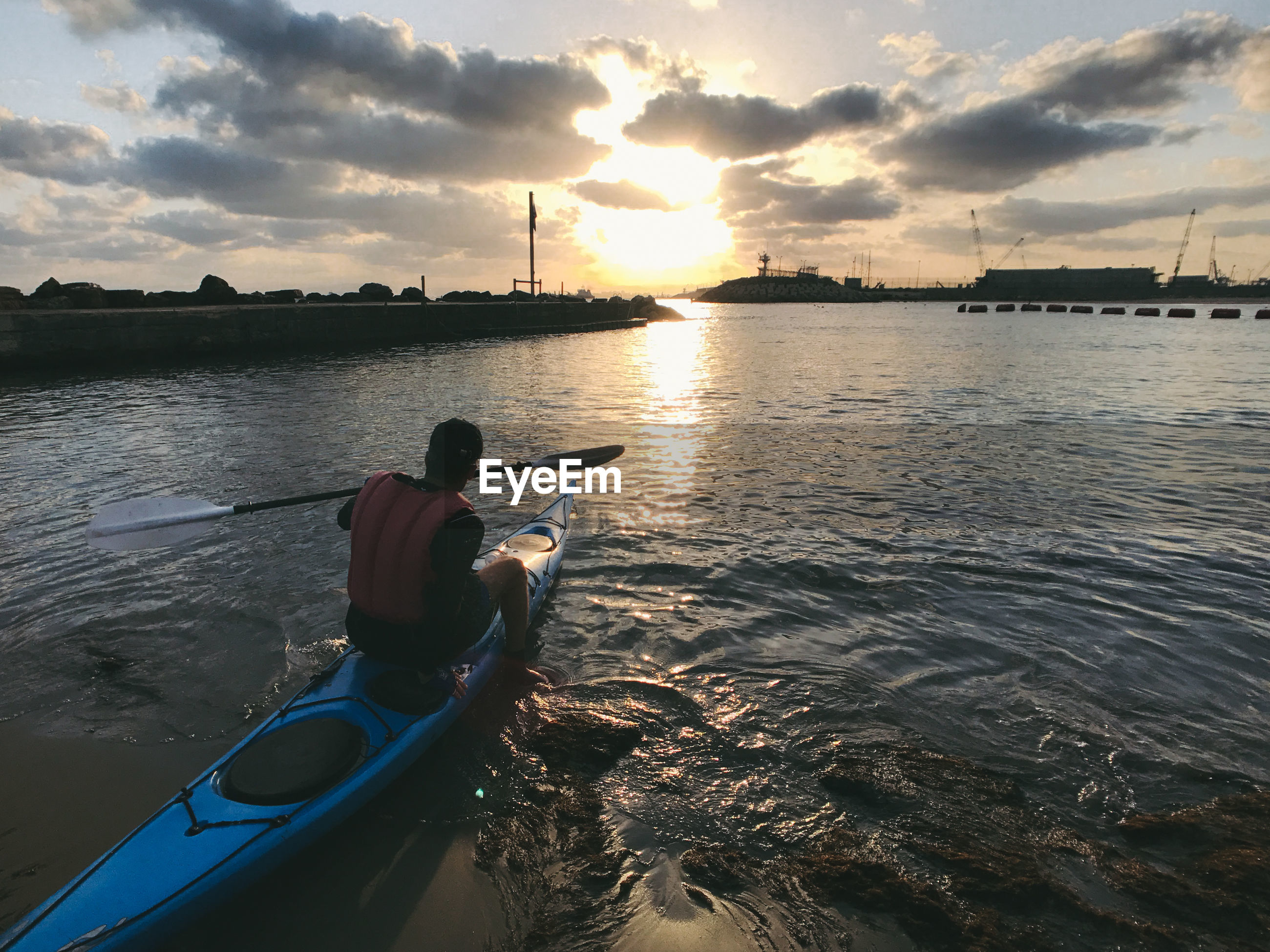 Rear view of man kayaking on sea against sky during sunset