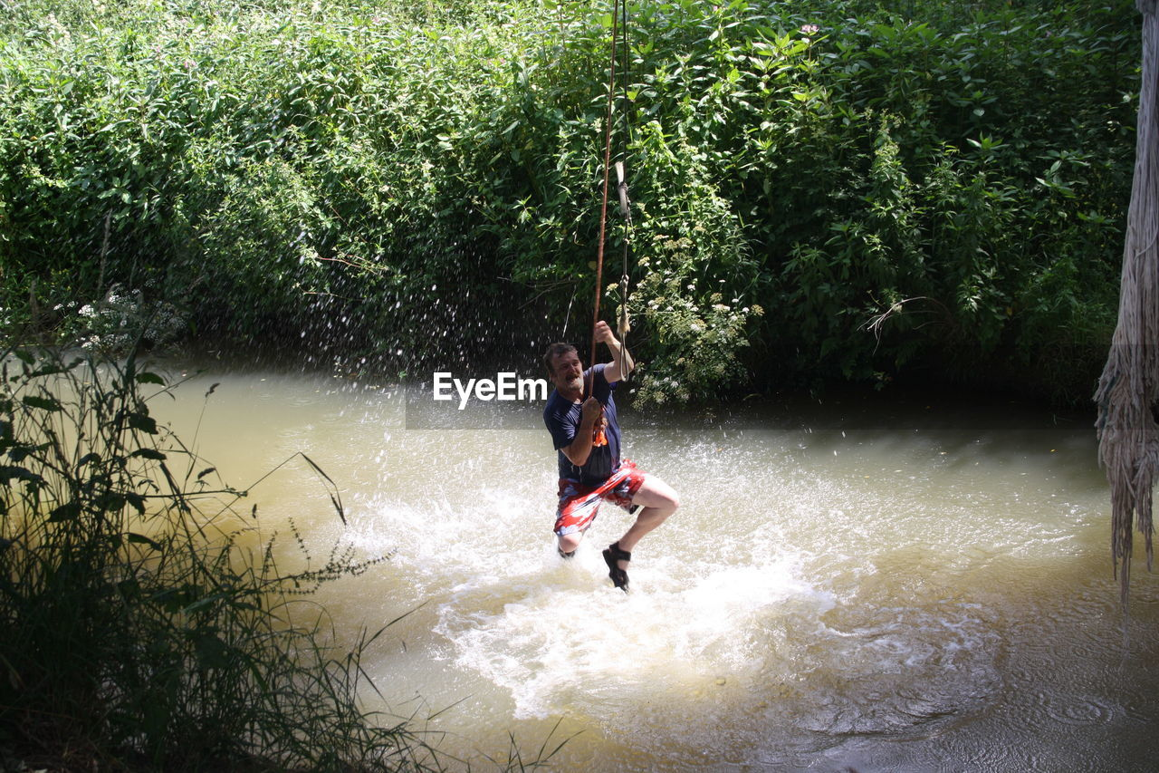 tree, real people, day, fun, leisure activity, outdoors, nature, river, full length, water, adventure, motion, lifestyles, enjoyment, one person, risk, extreme sports, hanging, beauty in nature, men, young adult, people