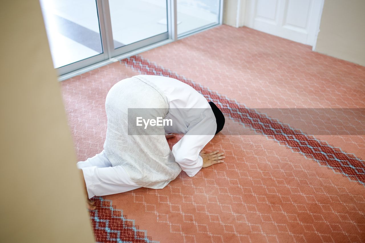 High angle view of man praying in room