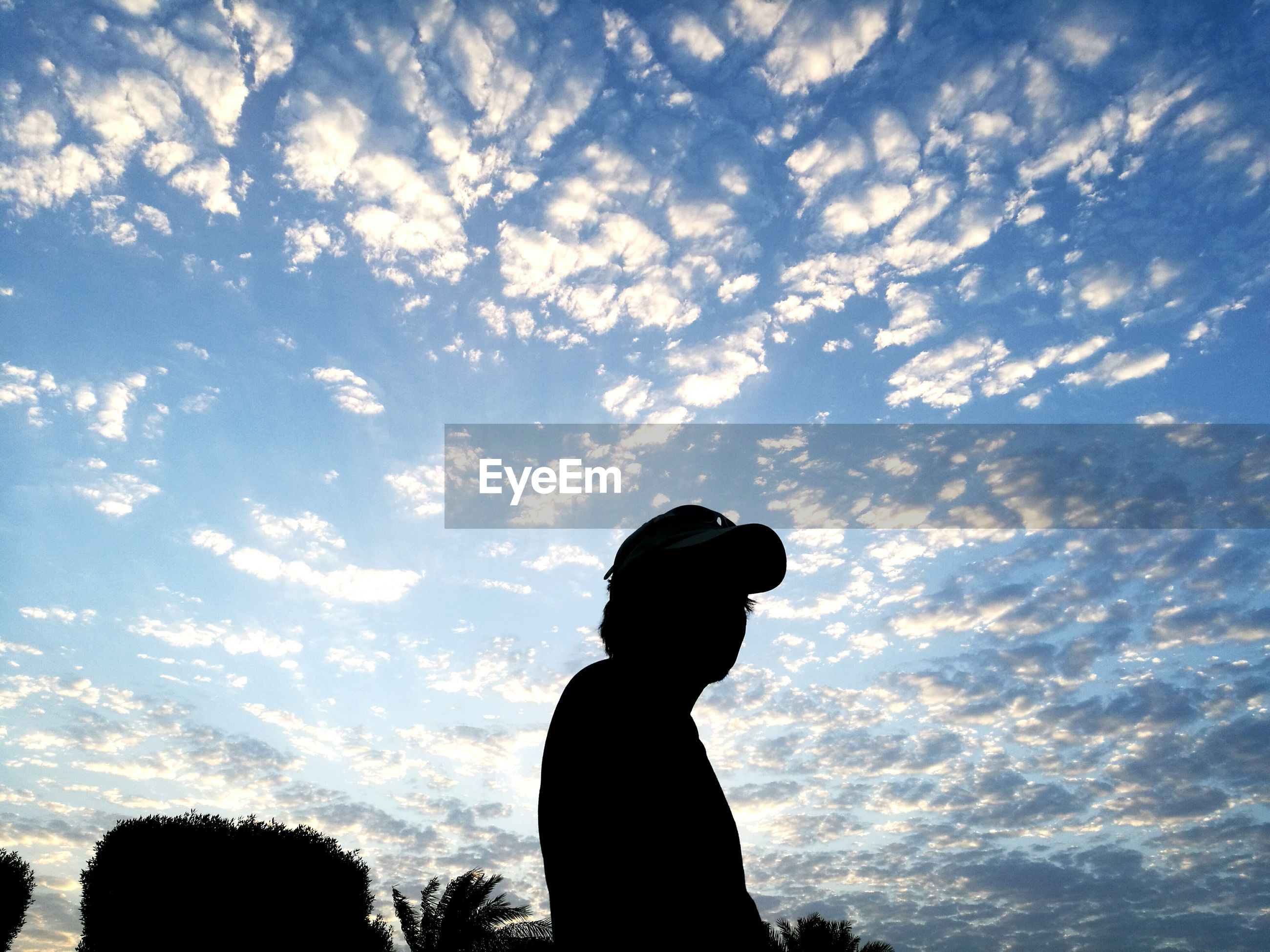Low angle view of silhouette man standing against sky during sunset