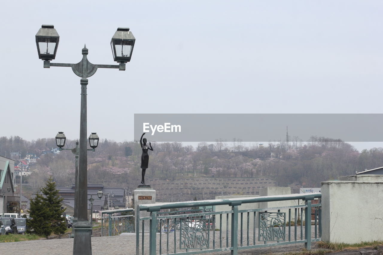 street light, sky, street, clear sky, nature, architecture, lighting equipment, city, day, built structure, no people, tree, building exterior, connection, outdoors, railing, plant, technology, copy space, bridge, cityscape, light