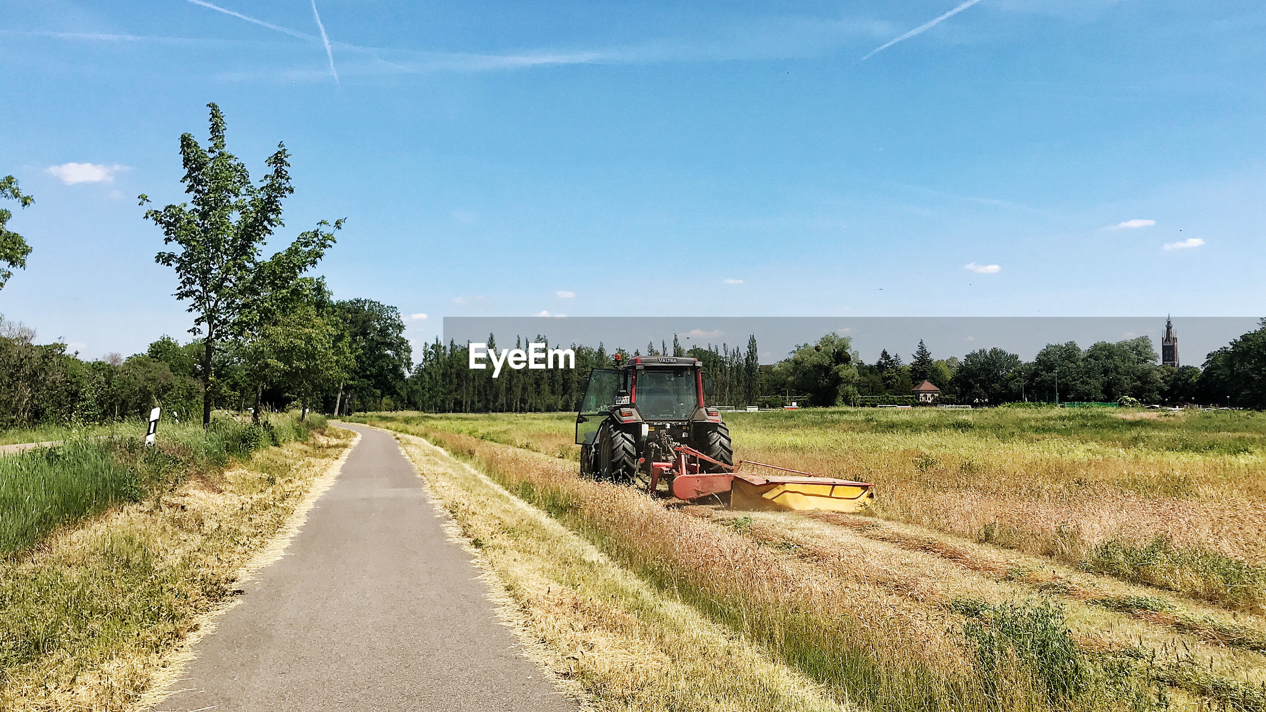 TRACTOR ON ROAD AMIDST FIELD