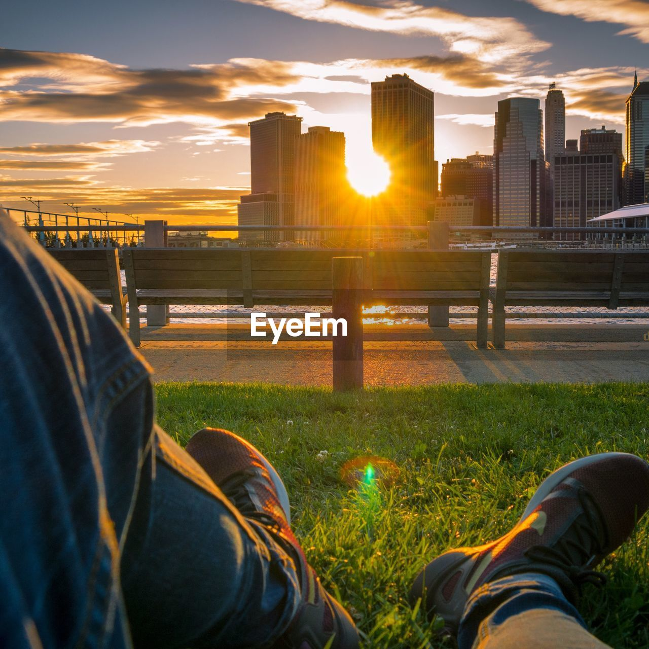 sunset, sky, grass, nature, built structure, orange color, cloud - sky, architecture, sun, real people, sunlight, one person, low section, plant, field, land, sunbeam, human leg, lifestyles, building exterior, body part, lens flare, outdoors, human foot