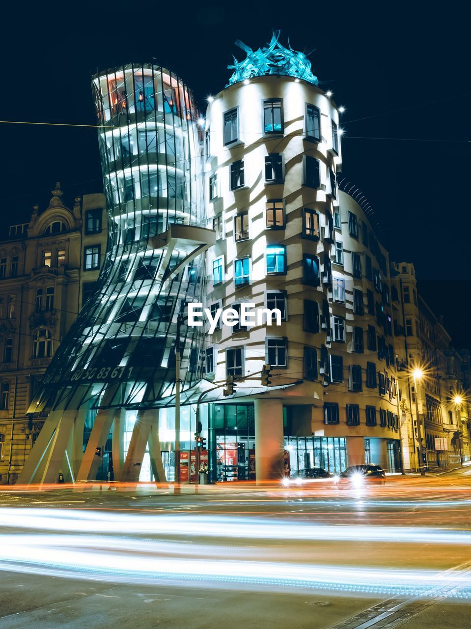architecture, city, built structure, building exterior, blurred motion, motion, illuminated, night, long exposure, street, road, speed, light trail, building, transportation, city life, no people, city street, outdoors, sign, office building exterior, skyscraper