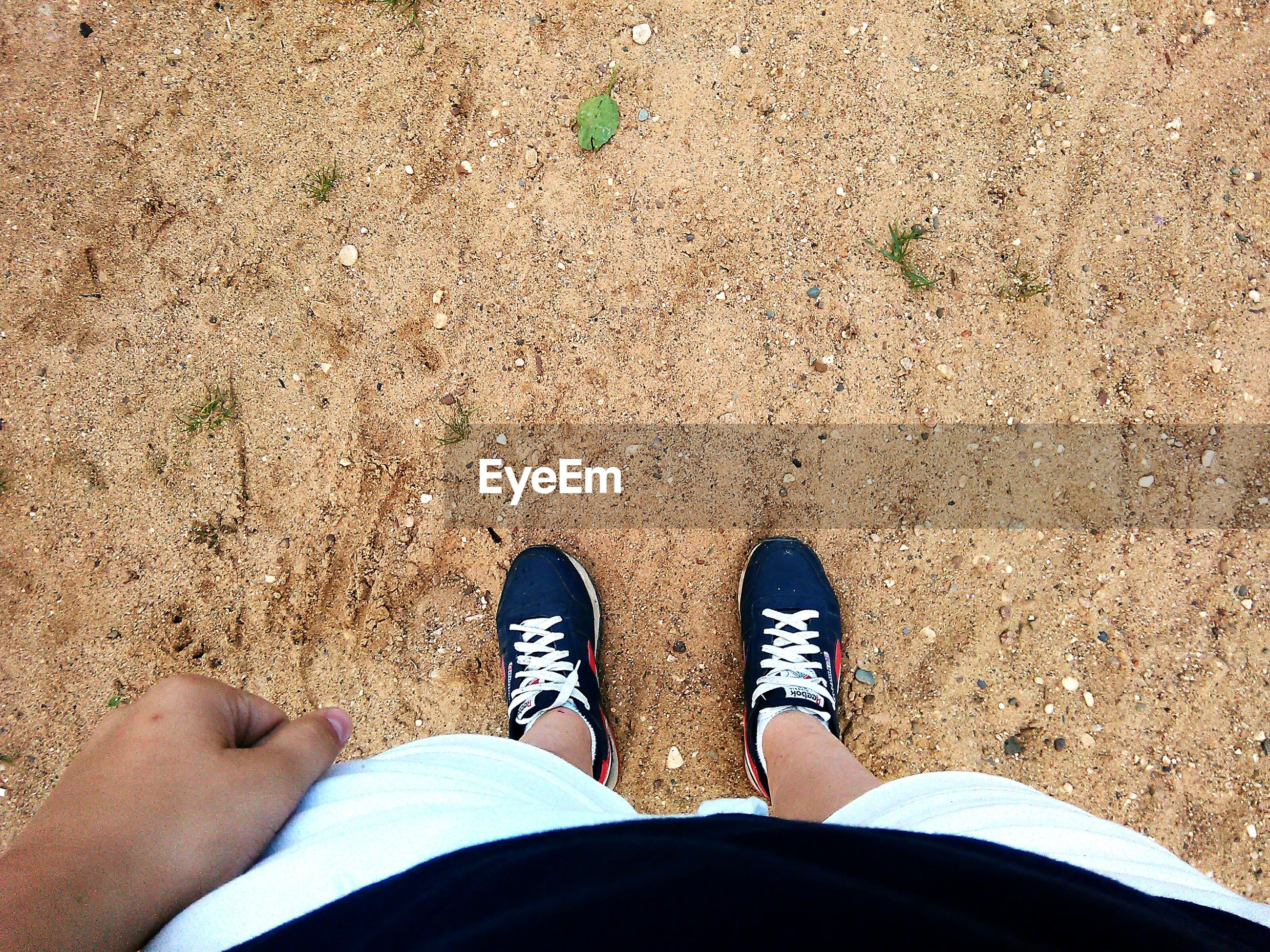 low section, person, personal perspective, high angle view, shoe, sand, human foot, beach, lifestyles, standing, leisure activity, directly above, footwear, men, part of, barefoot, unrecognizable person