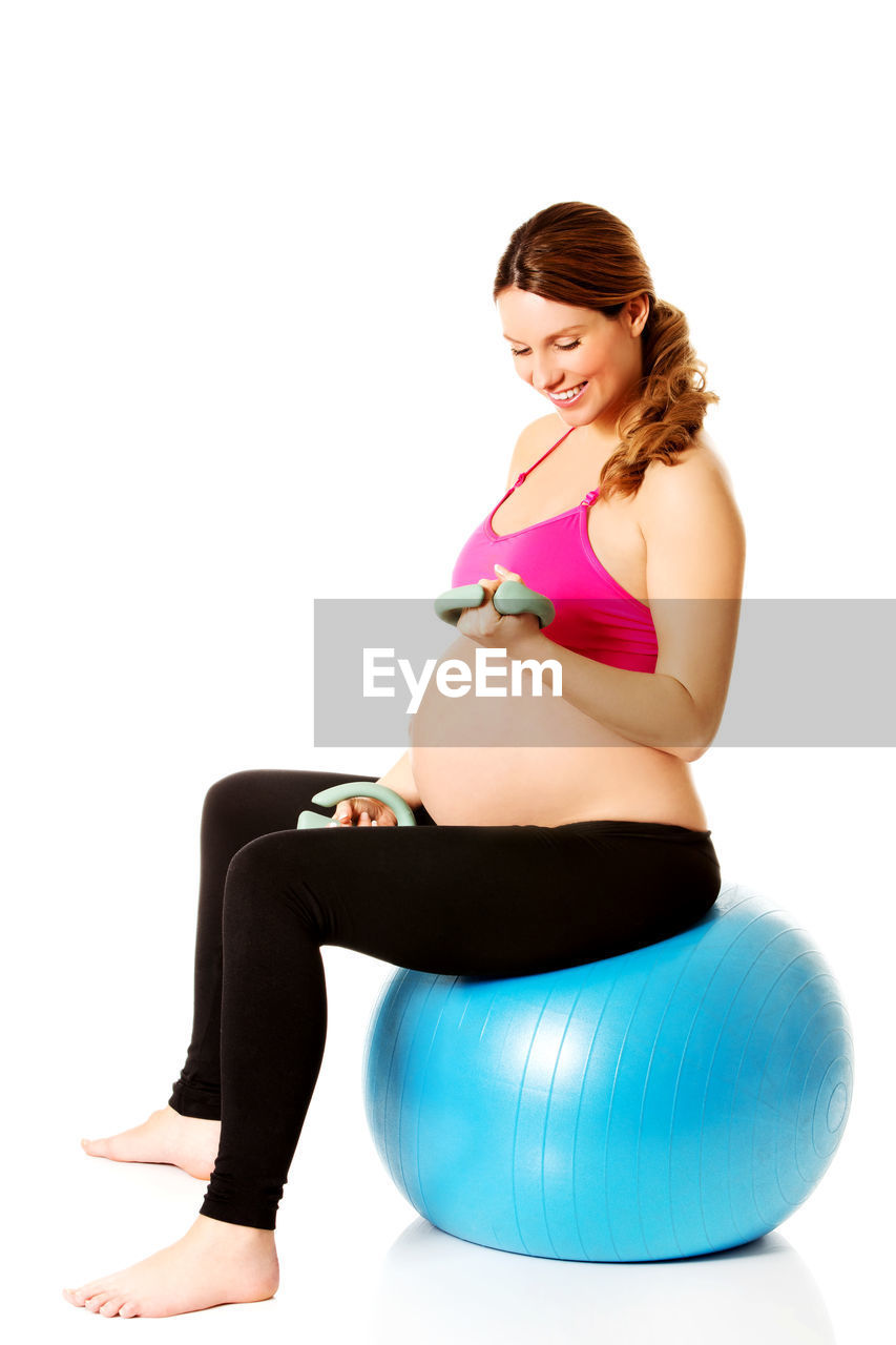 Pregnant Young Woman Sitting On Medicine Ball Against White Background