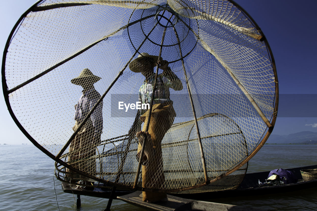 water, sky, fishing net, real people, nature, sea, transportation, one person, lifestyles, fisherman, nautical vessel, day, occupation, activity, men, fishing, standing, rear view, fishing industry, outdoors