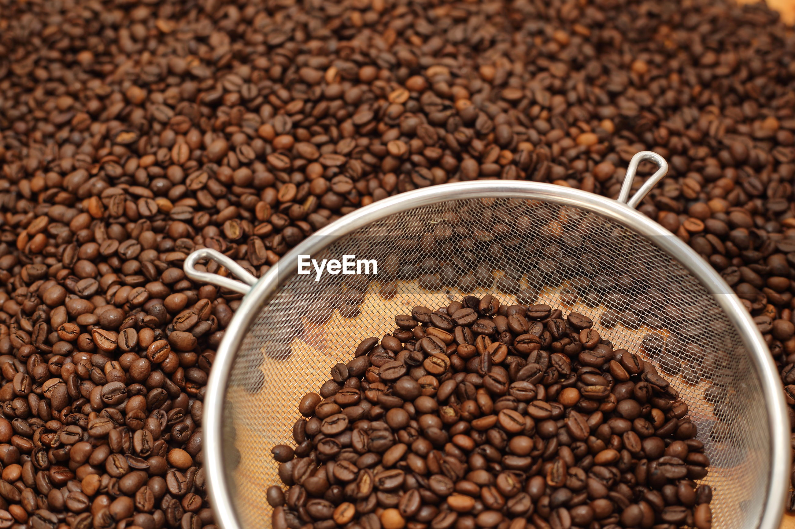 Full frame shot of coffee beans with colander on table