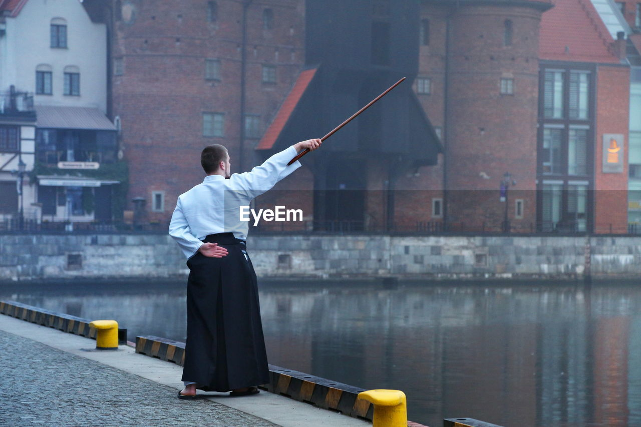 Man with stick standing by canal in city