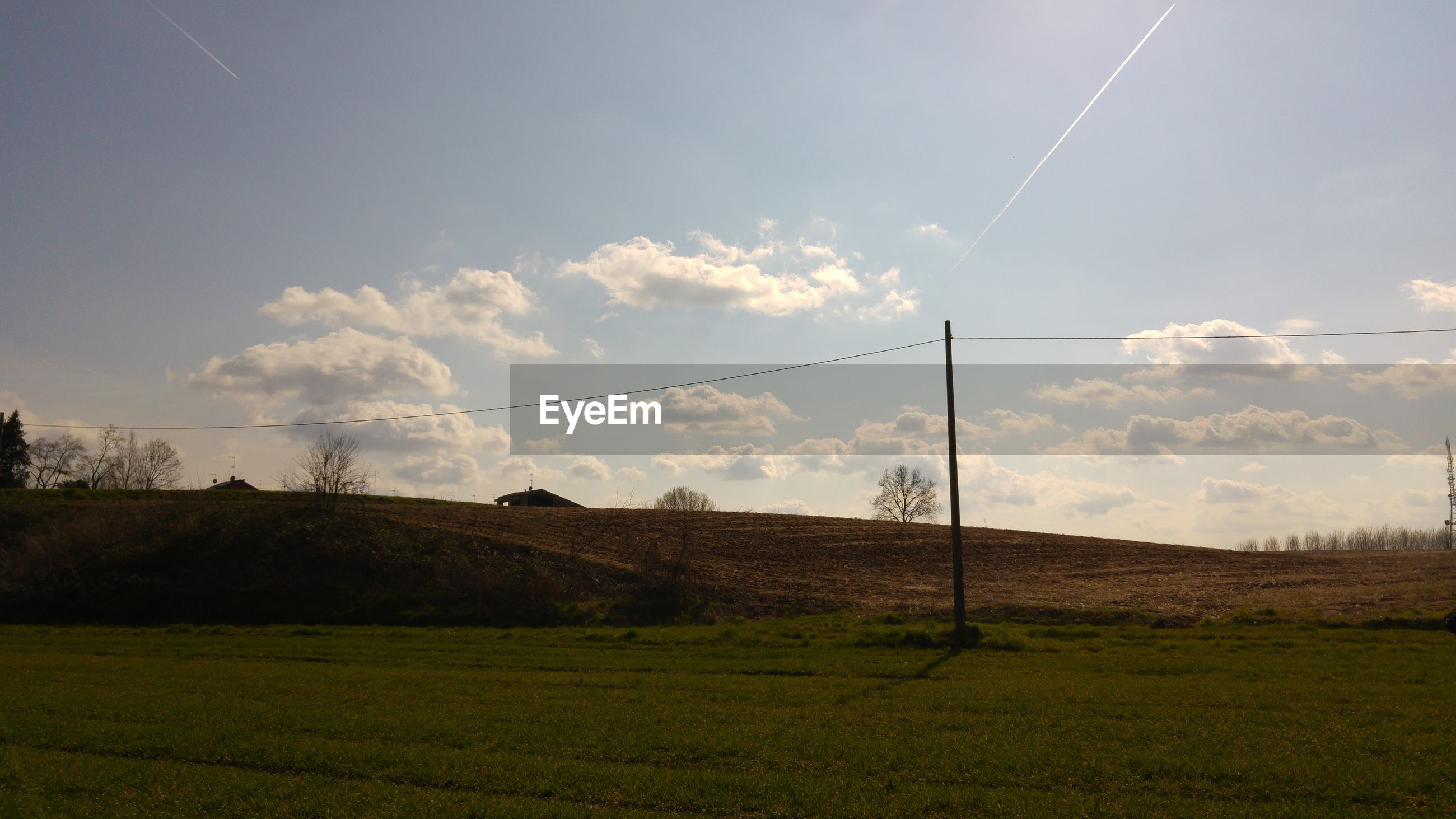 field, landscape, sky, tranquil scene, tranquility, grass, power line, electricity pylon, scenics, nature, beauty in nature, tree, electricity, rural scene, grassy, growth, cable, power supply, cloud - sky, non-urban scene