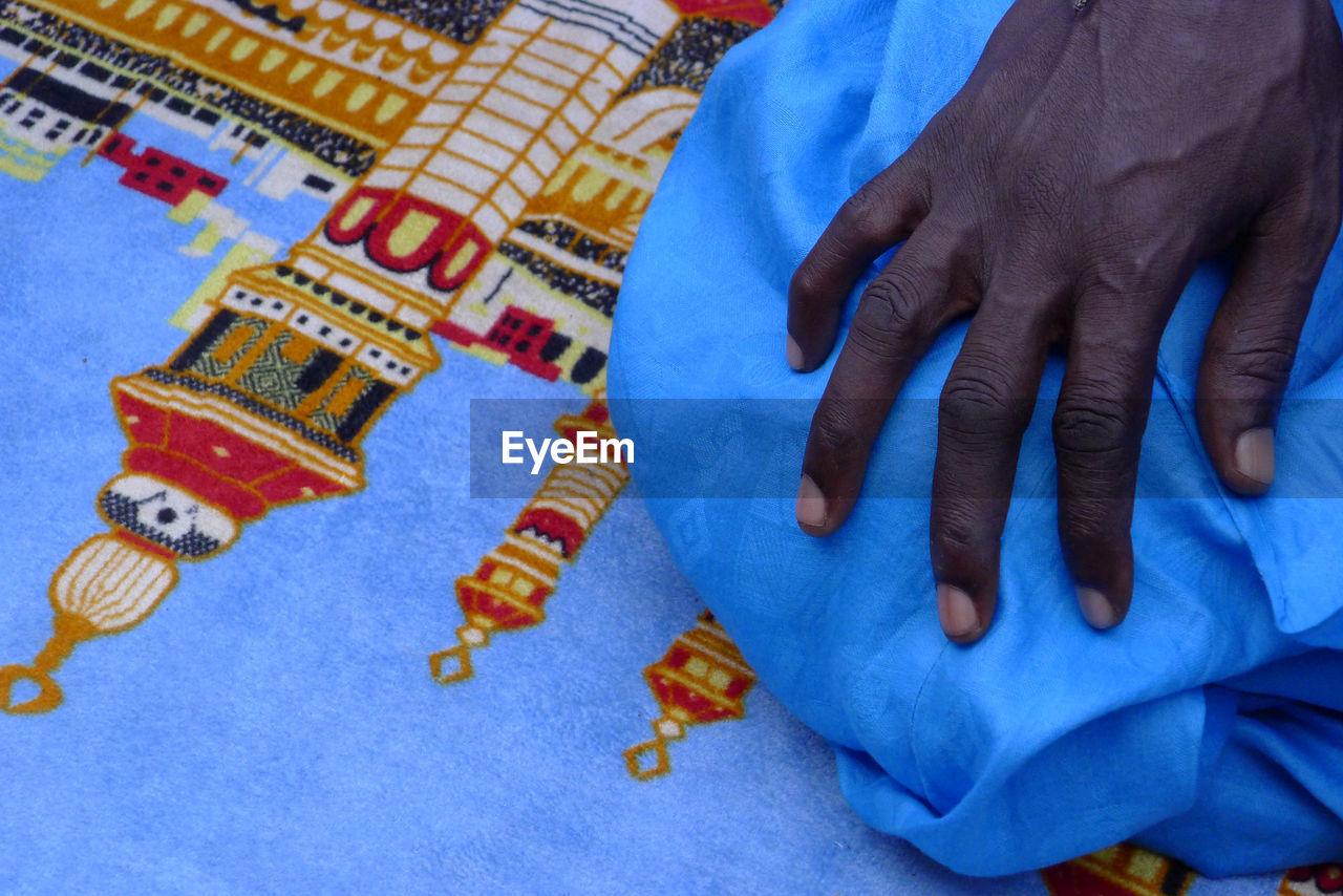 Cropped Hand Of Man Praying On Carpet