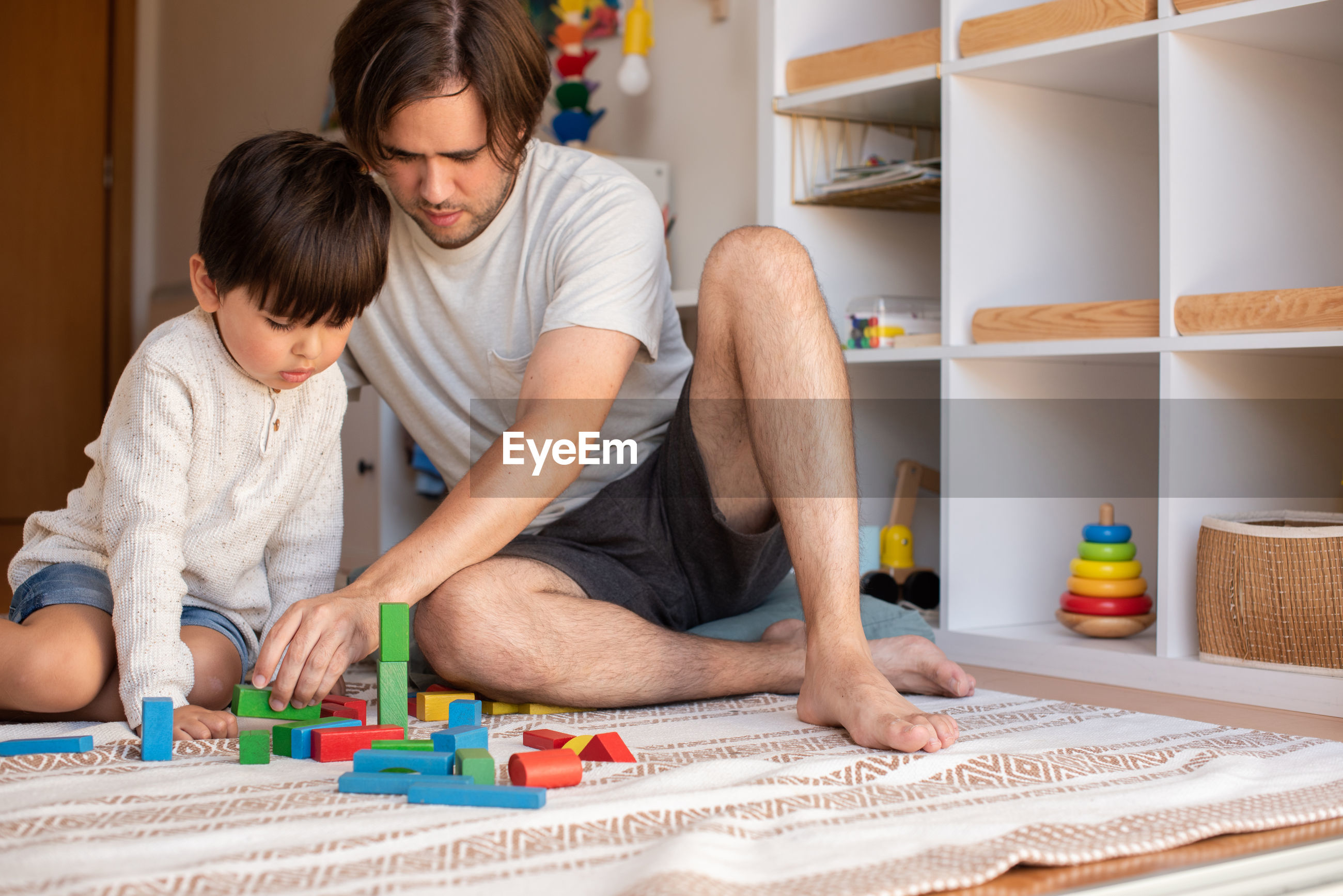 FATHER AND DAUGHTER SITTING ON TOY IN SHELF